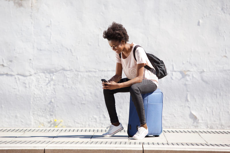 Young black female sitting on suitcase and using mobile phone outdoors. Full length portrait of young black female sitting on suitcase and using mobile phone royalty free stock image