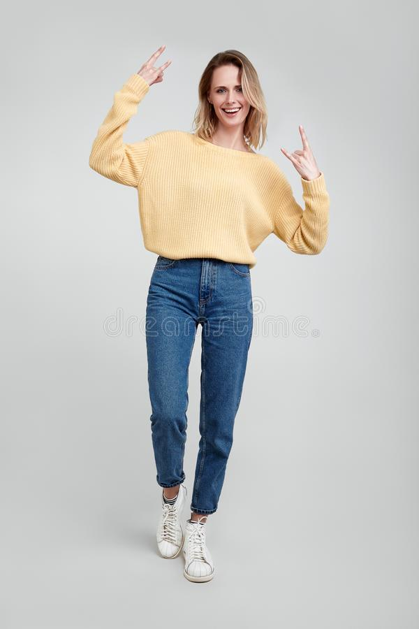 Full length portrait of a young blond woman showing rock gesture with hands isolated over gray background. dressed in casual royalty free stock photos