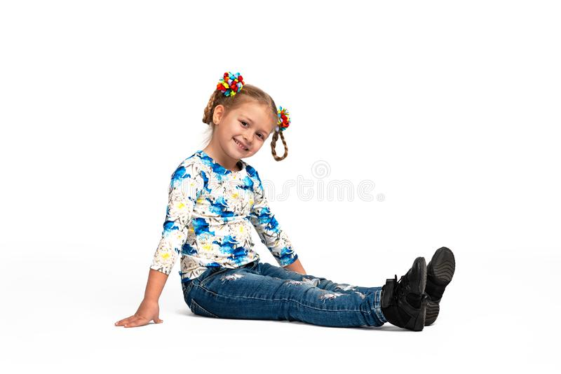 Studio portrait of young blonde smiling girl sitting on the floor against white background. Full length portrait of young blonde smiling girl wearing shirt with royalty free stock image