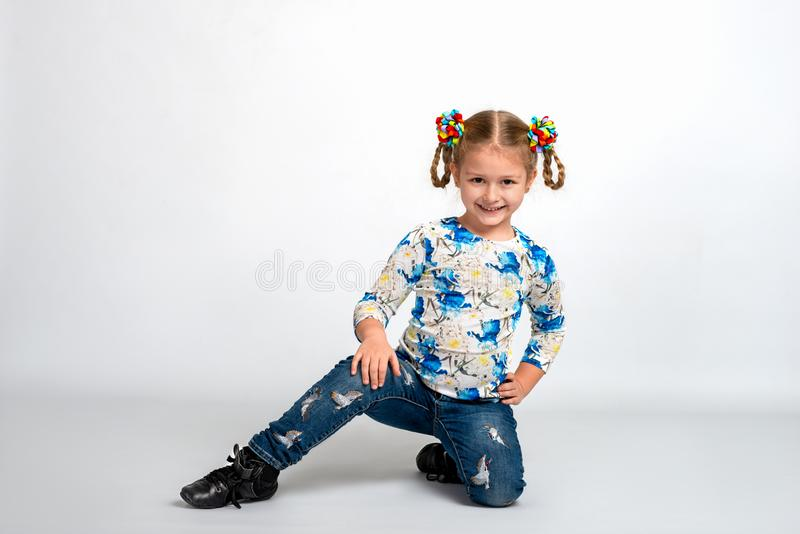 Studio portrait of young blonde smiling girl squatting on against white background. Full length portrait of young blonde smiling girl wearing shirt with print royalty free stock images