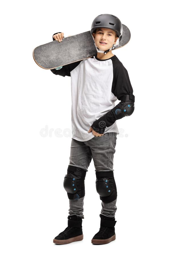 Young boy posing with a skateboard on his shoulder and a helmet stock images