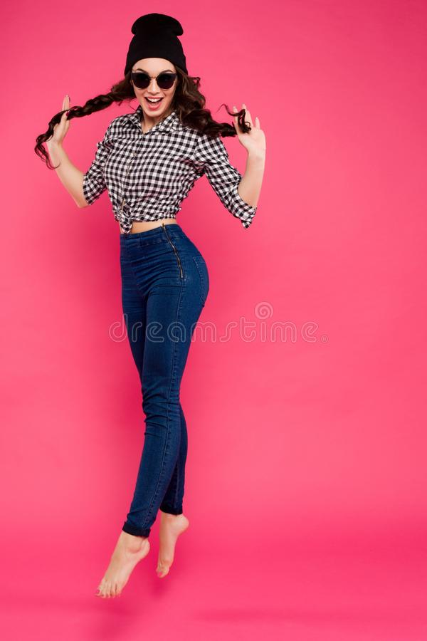 Full length portrait of young brunette girl in sunglasses jumping and holding her hair in hands. Smiling and emotion royalty free stock image