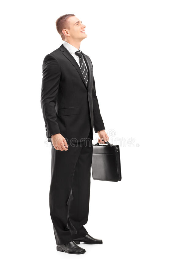 Full length portrait of a young businessman with briefcase looking upwards stock image