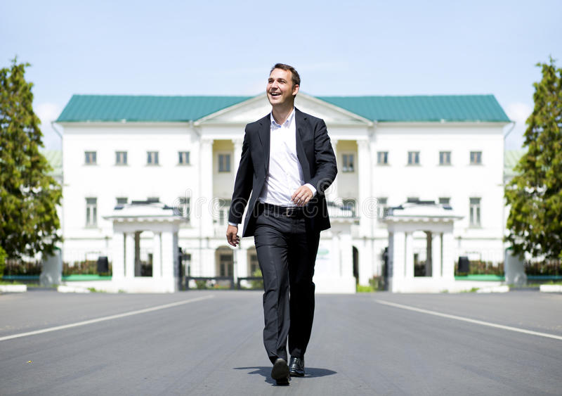 Full length portrait of a young businessman walking down the road royalty free stock photography