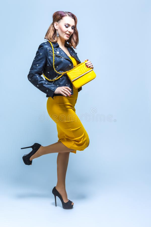 Full Length Portrait of Young Caucasian Fashionable Female Posing in Yellow Dress and Leather Jacket. Shot in Free Motion. Vertical Image stock image