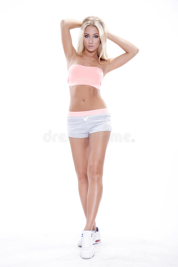 Full-length portrait of a young cheerful woman standing on gray stock photography