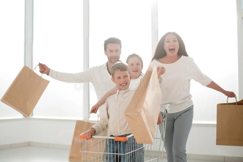 Full length portrait of a young family standing with shopping cart royalty free stock images