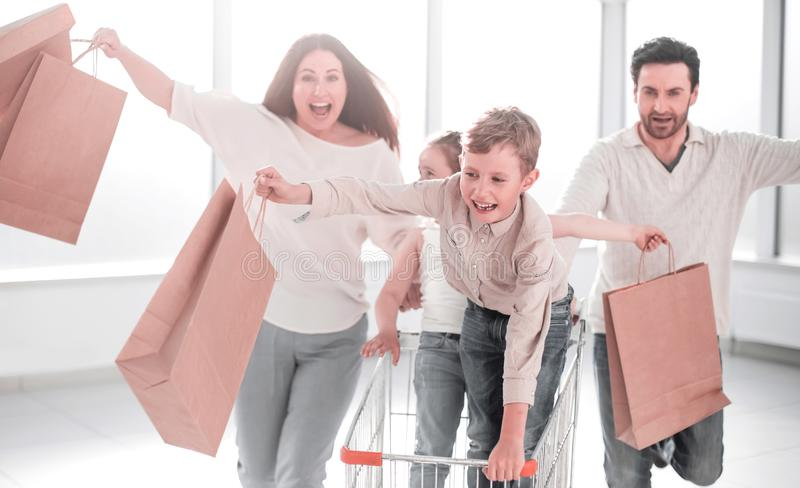 Full length portrait of a young family standing with shopping cart. Photo with copy space royalty free stock image