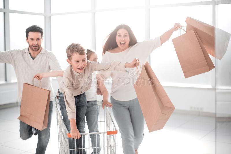 Full length portrait of a young family standing with shopping cart stock image