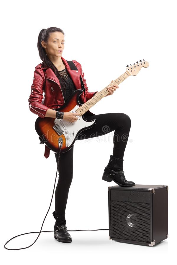 Young female guitarist standing next to an amplifier. Full length portrait of a young female guitarist standing next to an amplifier isolated on white background stock photography