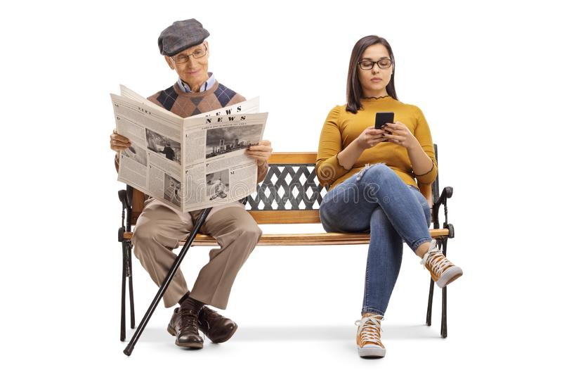 Young female with a mobile phone and a senior man reading a newspaper on a bench royalty free stock images