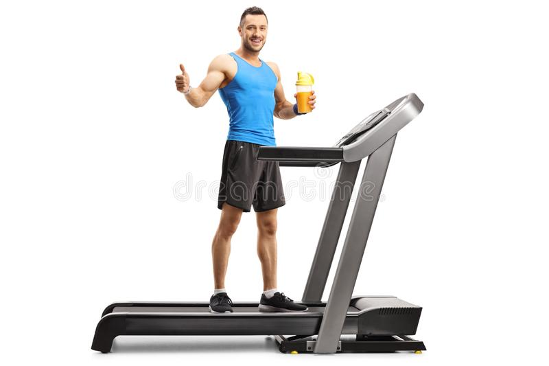 Young fit man on a treadmill holding a cup of sports energy drink and showing thumb up stock image
