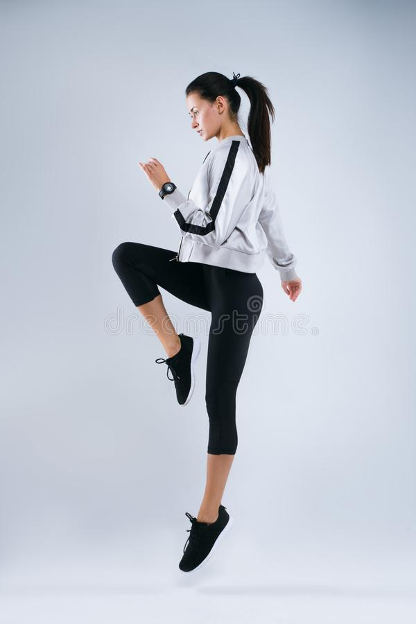Full length portrait of a young fitness woman in sportswear posing and jumping over gray background royalty free stock photo