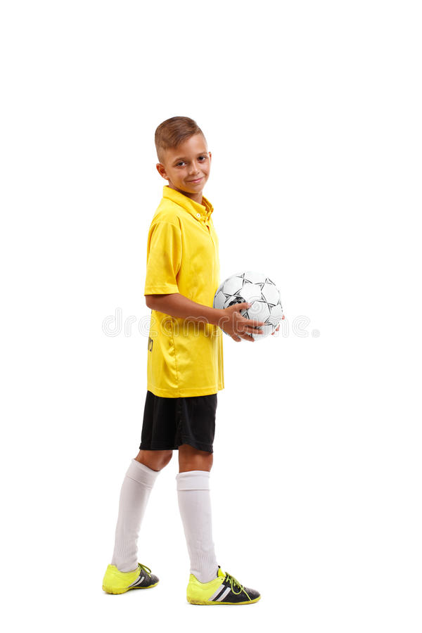 A full-length portrait of a young footballer in a yellow T-shirt holds in arms a ball isolated on a white background. stock photo