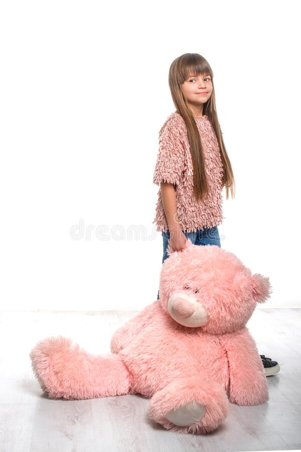 Shot  of a blonde young girl with long hair and bangs holding a big pink toy bear against white background in studio. Full length portrait  of a young girl with royalty free stock photography