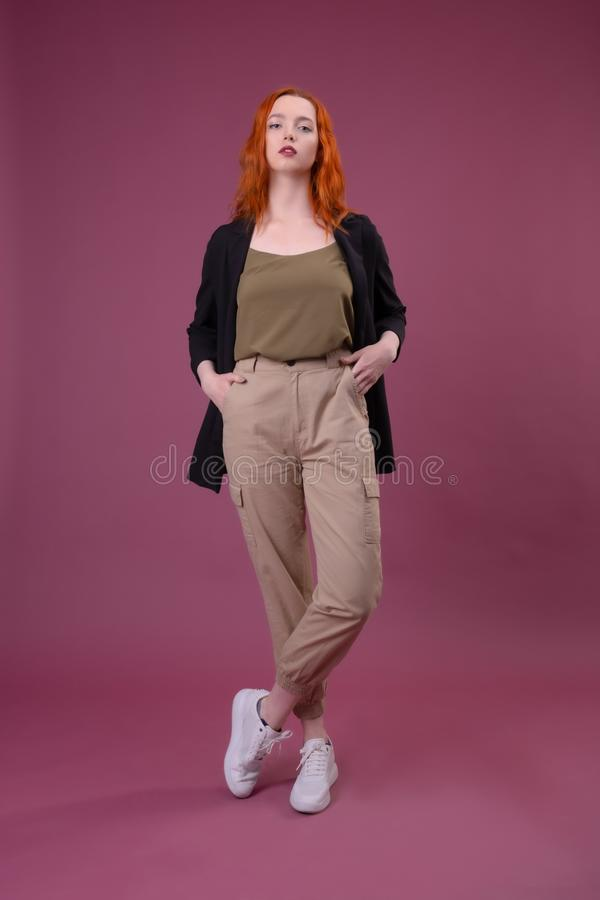 Full length portrait of a young girl standing over pink background stock images