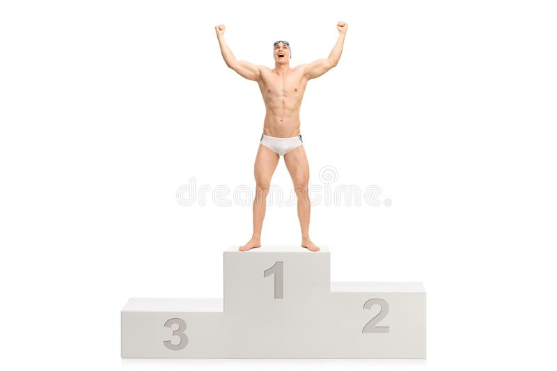 Young handsome swimmer posing on a winner`s pedestal stock image