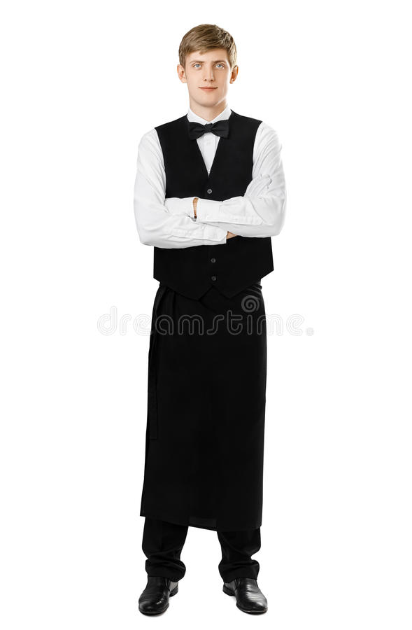 Full length portrait of young handsome waiter standing with crossed arms royalty free stock photography