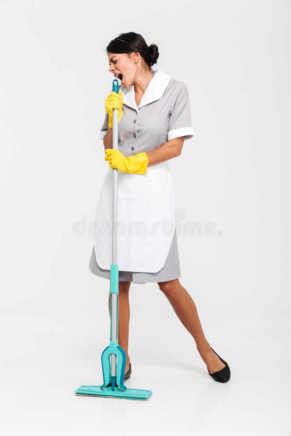 Full length portrait of young maid in gray uniform having fun while singing in mop as microphone royalty free stock photography