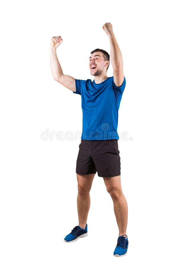 Full length portrait of young man athlete with hands raised, celebrating victory. Self overcome concept, achieving success. Sporty royalty free stock photo