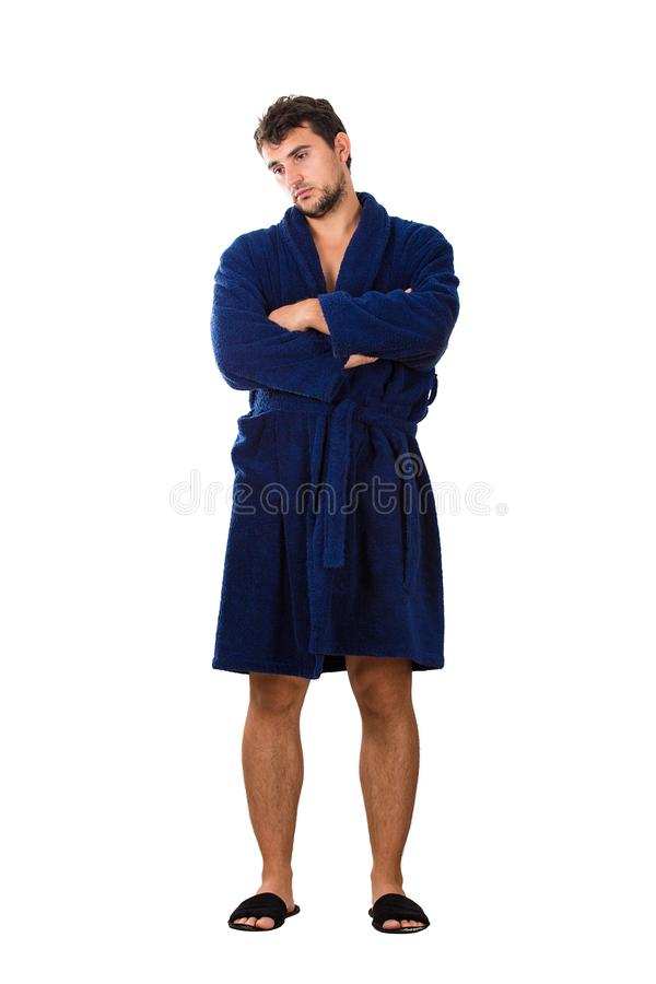 Full length portrait of a young man in a blue bathrobe holding arms crossed looking aside upset and tiredness emotion isolated on royalty free stock photos