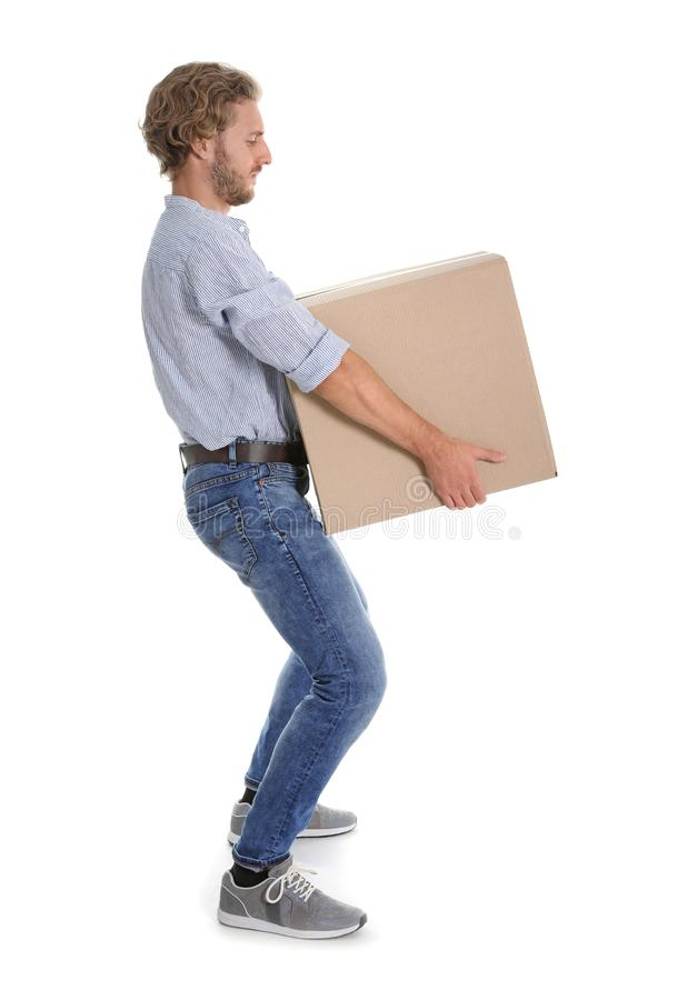 Full length portrait of young man carrying heavy cardboard box on white background royalty free stock photography