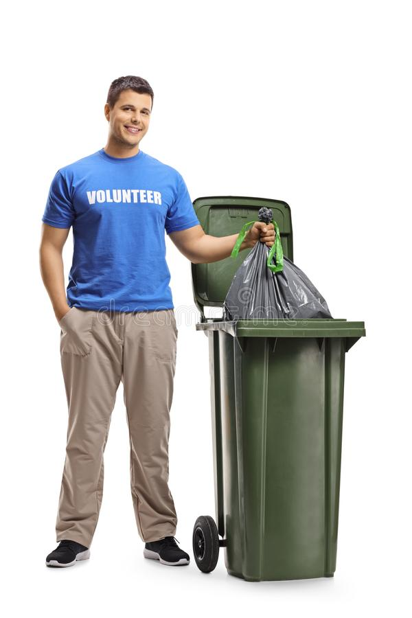 Young man volunteer throwing waste in a bin. Full length portrait of a young man volunteer throwing waste in a bin isolated on white background stock image
