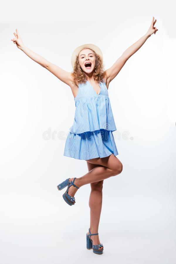 Full length portrait of a young playful woman wearing hat and dress posing with hands raised on one hand isolated over white backg. Full length portrait of a stock photography