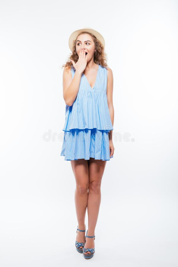 Full length portrait of a young pretty girl in summer dress and hat shocked isolated on white background royalty free stock image