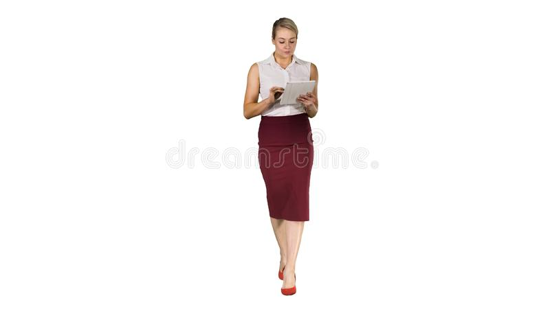 Young professional business woman using tablet computer and walking to the camera on white background. stock photography
