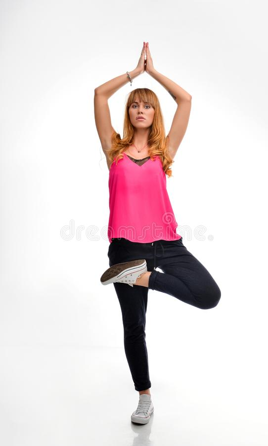 Full length portrait of a young red-haired fitness model in pink sportswear doing yoga or pilates exercise,  tree pose, stock photos