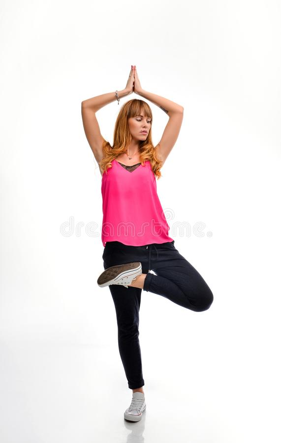 Full length portrait of a young red-haired fitness model in pink sportswear doing yoga or pilates exercise,  tree pose, royalty free stock images