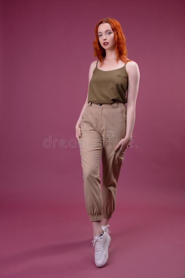 Full length portrait of a young girl standing over pink background stock photo