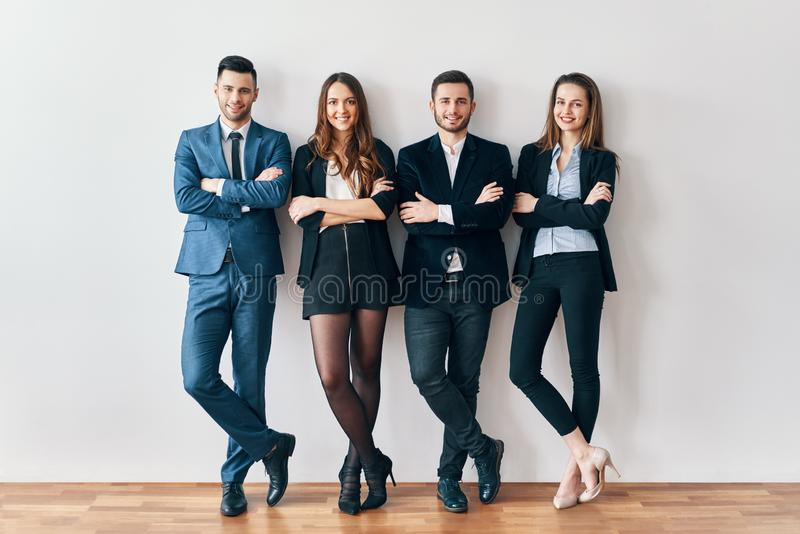 Full length portrait of young and smiling business people with arms crossed lean to wall in office royalty free stock photos