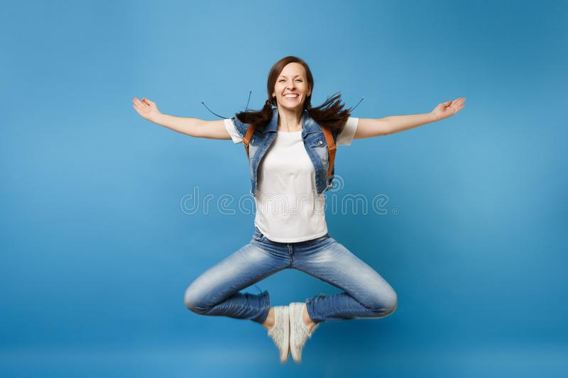 Full length portrait of young smiling woman student in denim clothes jumping spreading hands putting feets together royalty free stock image