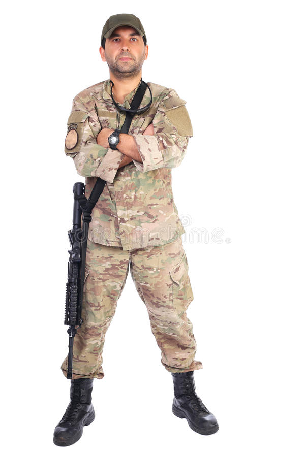 Full length portrait of young soldier in army clothes with gun a. Nd arms folded against white background royalty free stock photography