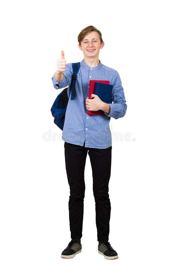 Full length portrait of young student boy holding two books to chest and carrying his backpack on the way to school. Teenager stock photos
