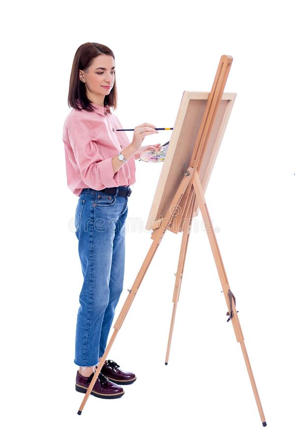 Full length portrait of young woman artist with easel, palette and paint brush painting picture isolated on white. Background stock photos