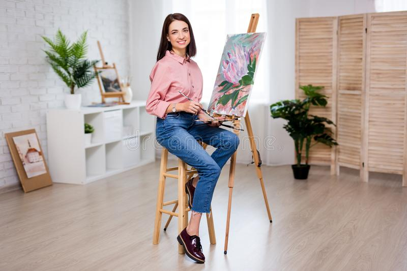 Full length portrait of young woman artist with easel, palette and paint brush painting picture at studio. Full length portrait of young woman artist with easel royalty free stock photography
