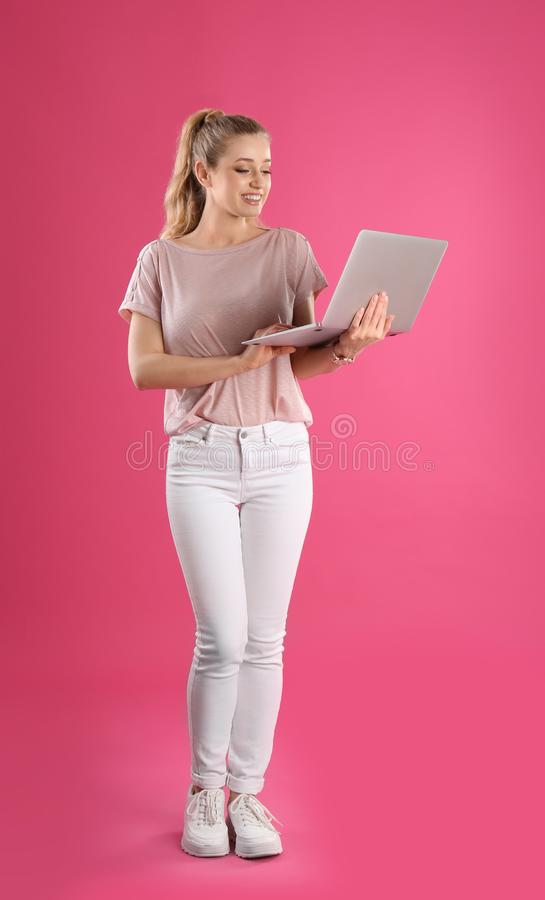 Full length portrait of young woman with laptop stock photos
