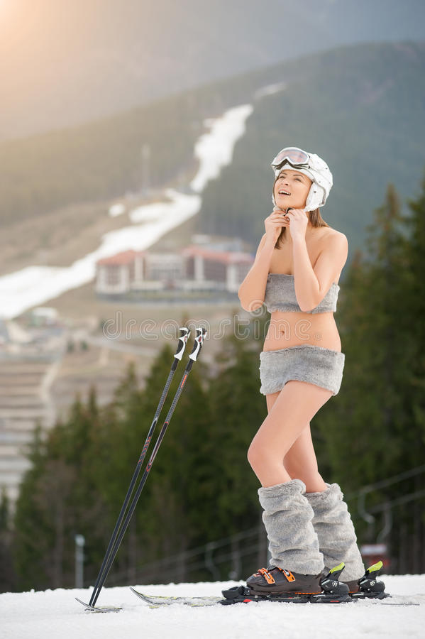 Full length portrait of young woman naked skier is putting on helmet. Ski resort, slope and forest background. Full length portrait of young woman naked skier is stock image
