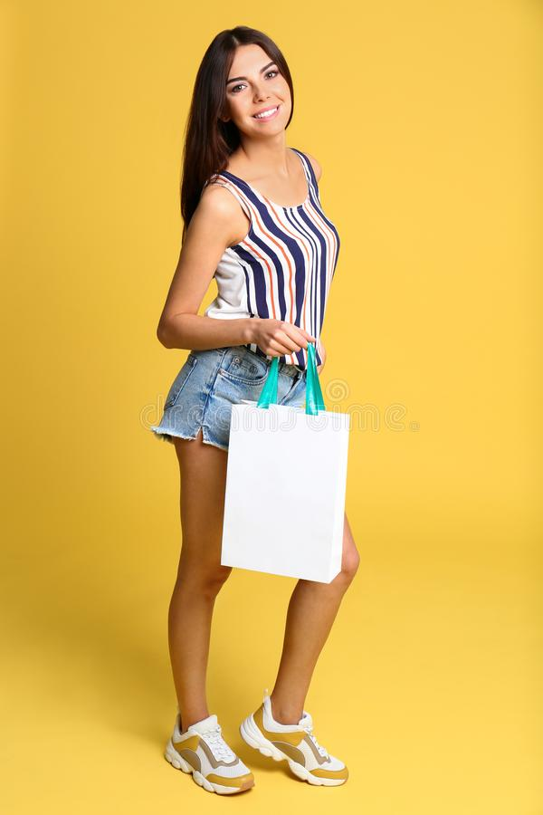 Full length portrait of young woman with paper bag on yellow stock photos