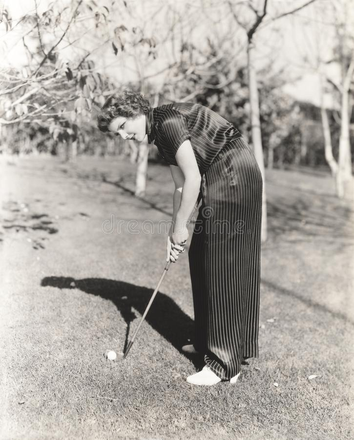 Full length portrait of young woman playing golf on field royalty free stock photo