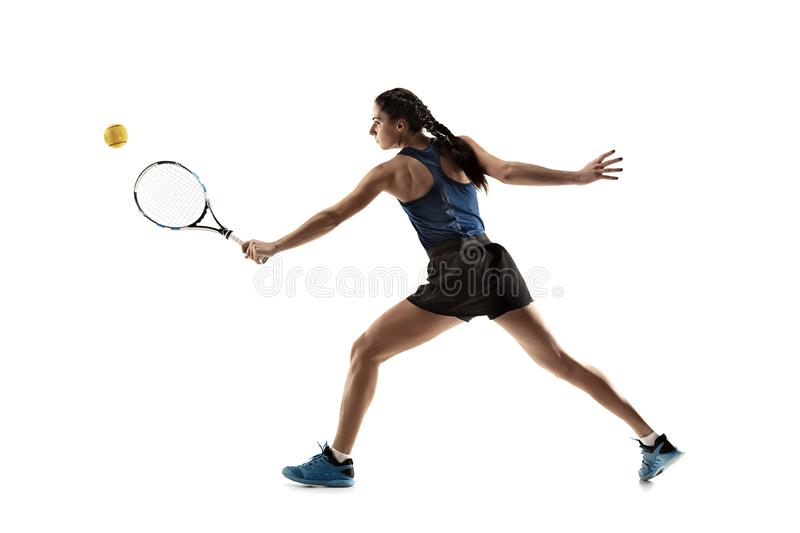 Full length portrait of young woman playing tennis isolated on white background royalty free stock image