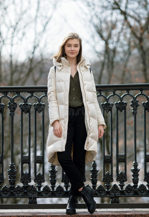 Full length posing beautiful young blonde woman standing on the spring city park in warm clothes. Cold season lifestyle freshness. Concept stock photos