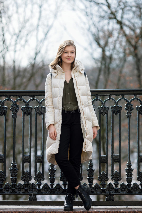 Full length posing beautiful young blonde woman standing on the spring city park in warm clothes. Cold season lifestyle freshness. Full length posing beautiful stock photos
