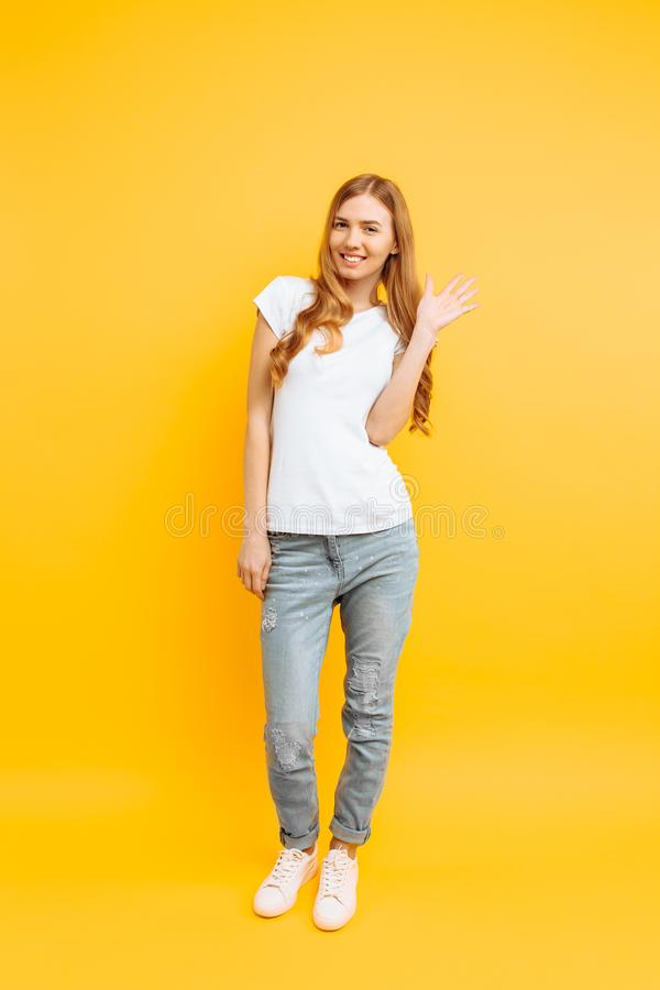 Full length, positive girl, shows a greeting gesture, on a yellow background royalty free stock image