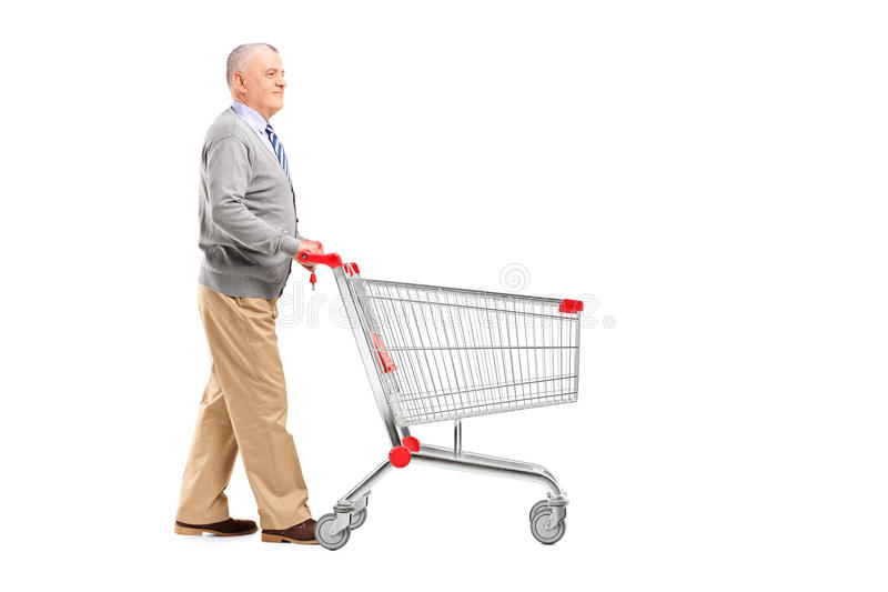 Full length potrait of a gentleman walking and pushing an empty. Shopping cart isolated on white background stock images