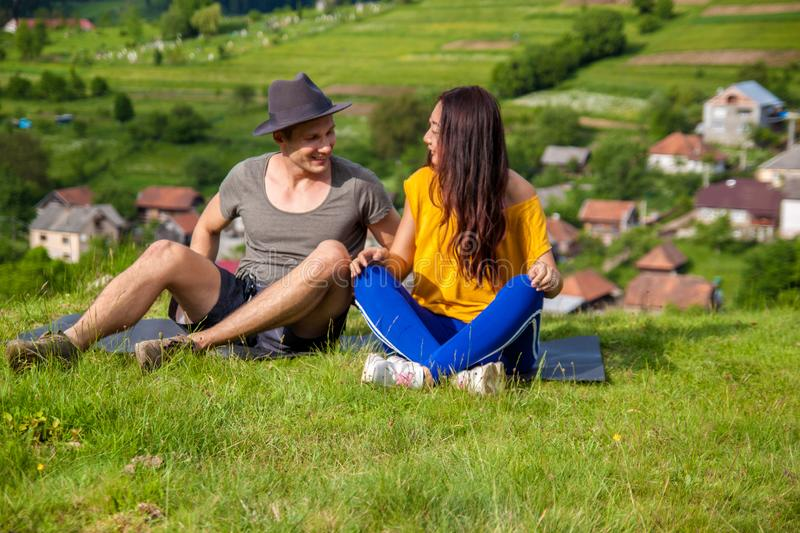 Full length of pretty girl and handsome man joyfully bounding to each other on green grass. Full length portrait of joyful girl and boy sitting on the mountain royalty free stock photography