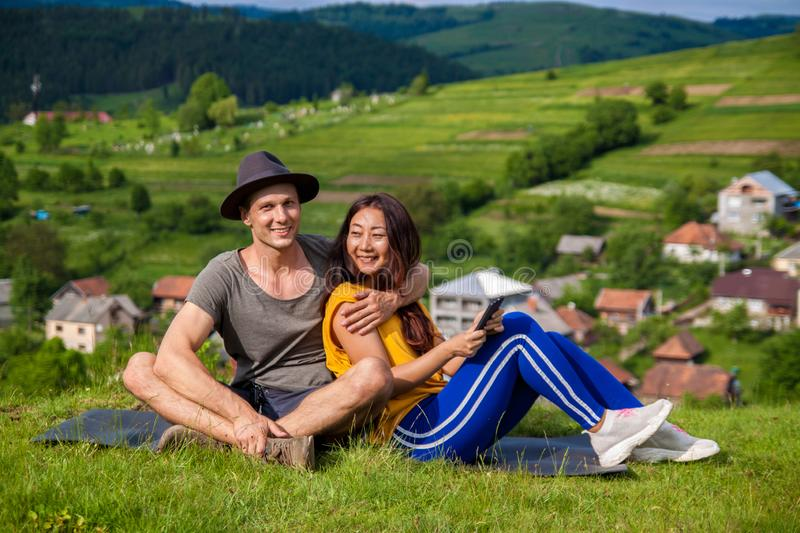 Full length of pretty girl and handsome man joyfully bounding to each other on green grass. royalty free stock photos